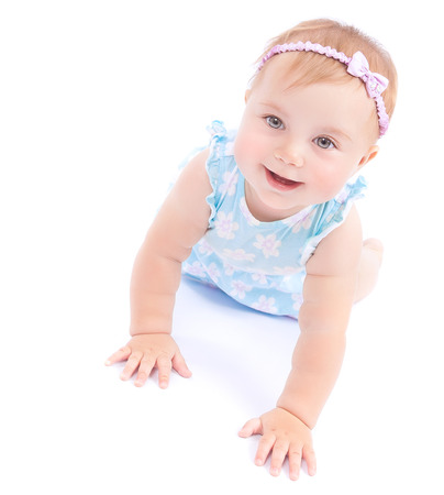 Cute joyful baby girl crawling in the studio, isolated on white background, active little child having fun, happy and carefree childhood concept