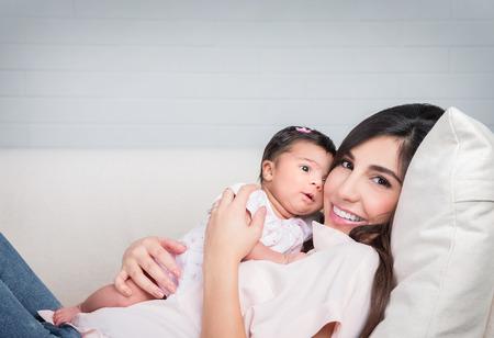 해피 어머니 집 소파에 누워 아기와 함께, 쾌활한 여자가 그녀의 사랑 스럽다 딸, 사랑과 행복 개념을 가지고 노는