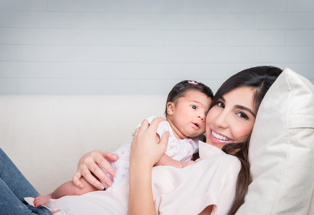 Happy mother with baby lying down on the couch at home, cheerful woman playing with her adorable daughter, love and happiness concept