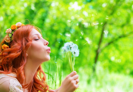 Closeup portrait of pretty woman blowing on dandelion, having fun on fresh green park in sunny day, enjoying spring season