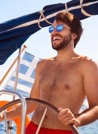 Happy guy behind wheel of sailboat, sexy joyful shirtless sailor enjoying riding on luxury water transport, active summertime adventure