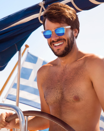 shirtless guy: Portrait of cheerful captain behind wheel of luxury sailboat, sexy man wearing stylish sunglasses and enjoy interesting water trip, happy summer vacation concept