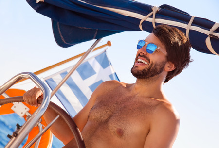 skipper: Portrait of cheerful captain behind wheel of luxury sailboat, sexy man wearing stylish sunglasses and enjoy interesting water trip, happy summer vacation concept