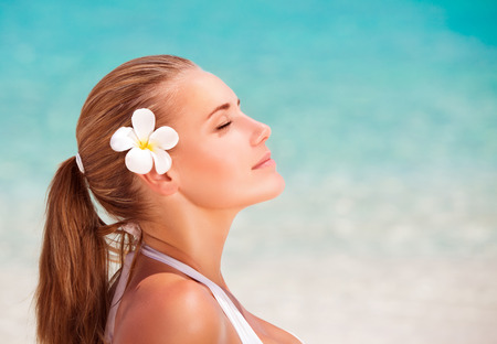 Side view portrait of beautiful calm female with frangipani flower in hair meditating on the beach, enjoying day spa, summer vacation and relaxation Stock Photo