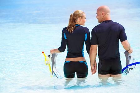 물에 서서 다이빙을 준비하고, 극단적 인 스포츠와 활동적인 여름 휴가를 즐기고 행복 다이버 커플의 뒷면 스톡 콘텐츠