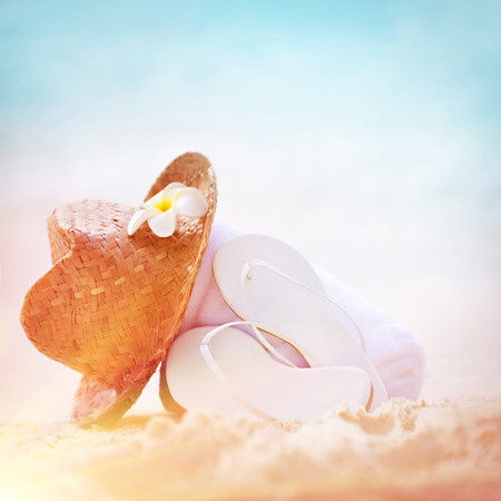 spa stuff: Summer holidays background, closeup photo of stylish beach items on sandy seashore, nice straw hat white flip flops, necessary accessories for summer vacation on beach resort Stock Photo