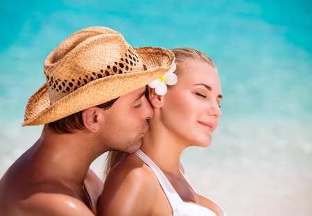 guy on beach: Portrait of handsome man kissing his nice young wife, closed eyes of pleasure, enjoying each other on the beach, summer vacation on exotic resort