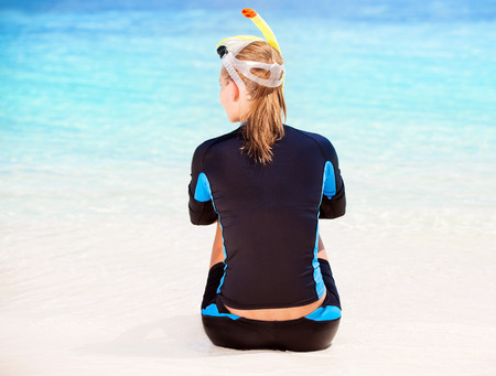 Back side of calm diver girl sitting on seashore, wearing snorkeling equipment and resting on the beach, summer adventure and traveling concept photo