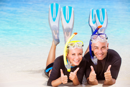 Joyful diver couple lying down on the beach, wearing mask and flippers for snorkeling, gesturing by hands good mood, active summer time vacation Banque d'images