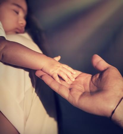 Closeup Foto von cute little Baby auf Mütter Hände berühren fatherd Hand, helle Strahlen der Sonne scheint auf ihre, Gottes Segen, Hoffnung und Rettungskonzept