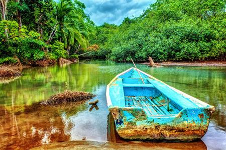 Oude boot in tropische rivier, een perfecte plek om te vissen, exotische zomer avontuur, prachtige natuur van het Nationale Park van Costa Rica, Midden-Amerika Stockfoto