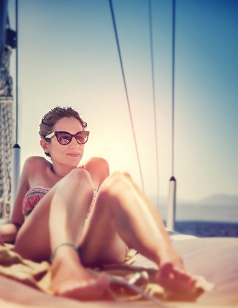 sailboat: Sexy woman on sailboat lying down on the deck of luxury sailboat, tanning on bright sun light Stock Photo