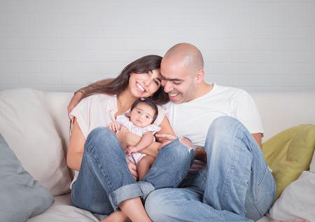 los padres jóvenes disfrutando de tiempo dedicado a su hija recién nacida adorable