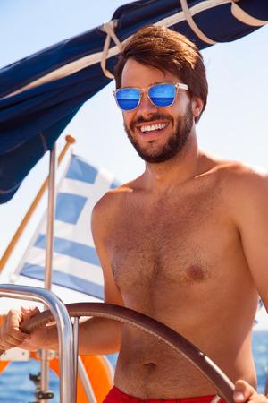 Portrait of handsome captain driving luxury sailboat, enjoying amazing sea journey photo
