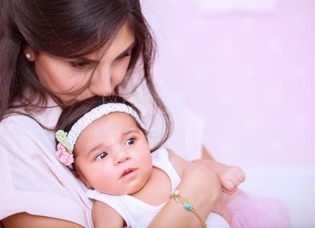 gentleness: Closeup portrait of beautiful woman with gentleness kissing her cute newborn daughter, enjoying parenthood, mother Stock Photo