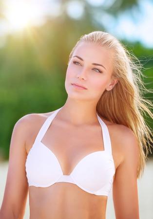 Portrait of beautiful blond girl on the beach standing on bright sun light photo