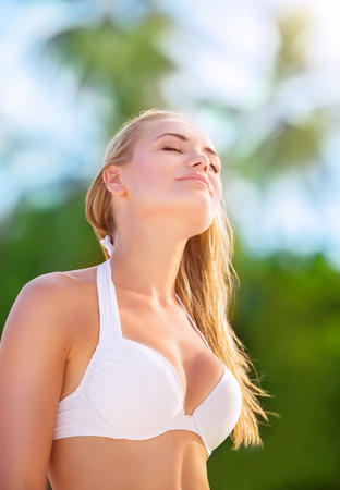 Portrait of beautiful blond girl on the beach with closed eyes of pleasure enjoying sunny day photo