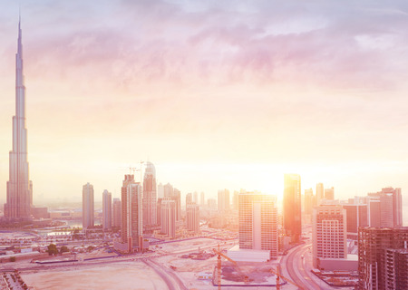 morning sunrise: Beautiful sunset over Dubai city, amazing cityscape lit with warm sun light