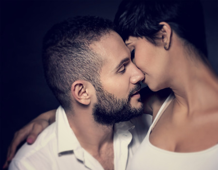 enamorados besandose: Primer retrato de gentil pareja de enamorados bes�ndose aislado en negro, disfrutando rom�ntica relaci�n, afecto y concepto de la ternura