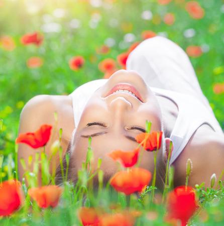 Mooi jong meisje liggend op verse papaver bloem veld, sluiten de ogen van plezier, genieten van verbazingwekkende de lente zonnige dag Stockfoto