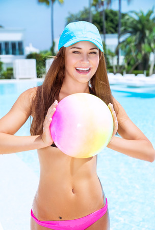 ball on water: Happy woman playing with ball in swimming pool on luxury beach resort, enjoying active water game, summer vacation concept Stock Photo
