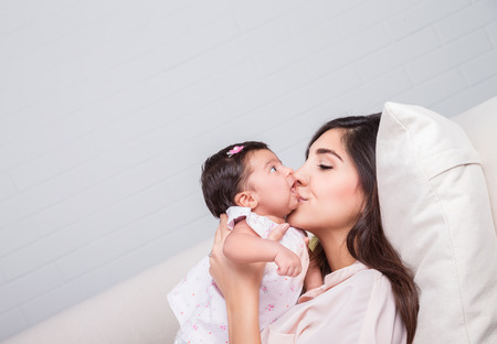 Happy mother kissing baby, cheerful joyful mom lying down with her adorable daughter on the couch at home, loving young family photo