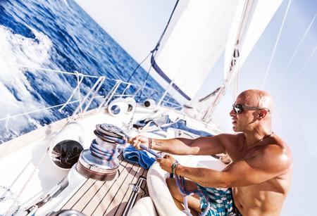 voile: Bel homme travaillant sur voilier, tirant sur la corde, les vacances d'�t� actif sur le transport de l'eau, avoir du plaisir dans la mer, la pratique sportive, de l'eau