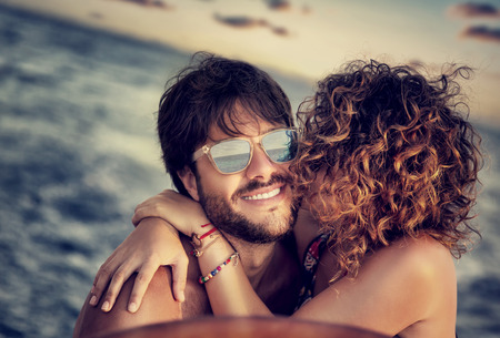 beach kiss: Closeup portrait of cheerful happy lovers on sailboat, young couple kissing and having fun in romantic cruise, love and enjoyment, summer vacation and holidays Stock Photo