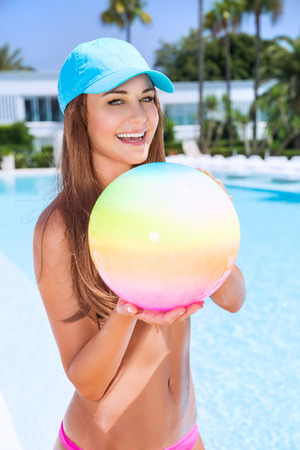 fun activity: Happy woman with ball in swimming pool, having fun on beach resort, enjoying summer activity, playing water game, vacation and enjoyment concept