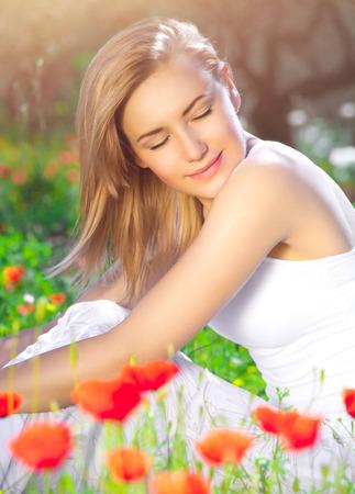 ojos cerrados: Calma hembra rubia sentado en campo de flor de amapola, la mujer con los ojos cerrados disfrutando disfruta de la belleza de la naturaleza, la relajación en el campo