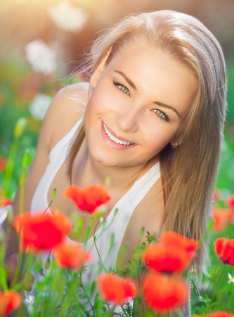 woman lying down: Beautiful woman lying down on fresh red poppy flowers field, enjoying beauty of countryside nature, relaxation and pleasure in the summer garden