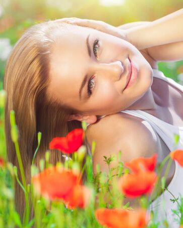 woman lying down: Beautiful woman lying down on fresh red poppy flowers field, enjoying beauty of countryside nature, relaxation and pleasure concept Stock Photo