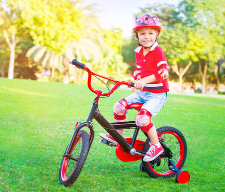 summer sport: Cute little boy riding a bike in the park in bright sunny day, spending leisure time outdoors, enjoying summer sport, happy childhood concept