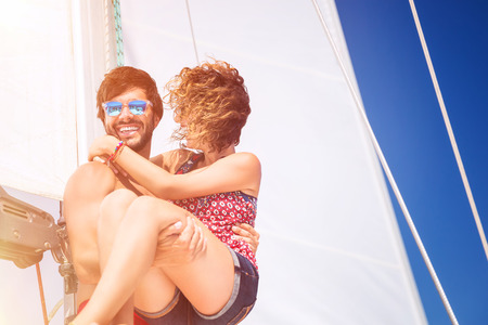 man carrying: Joyful couple on sailboat, handsome man carrying on hands his lovely girlfriend, spending honeymoon vacation in the sea, active summer time vacation
