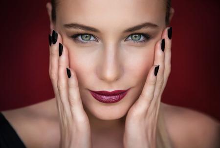 Közeli portré gyönyörű divatmodell fölött sötét piros háttér, csinos nő, elegáns smink, kozmetika