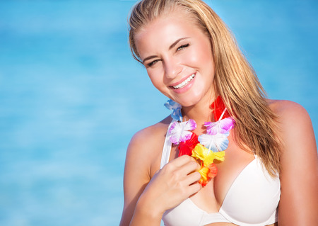 leis: Portrait of cute blond female wearing beautiful Hawaiian leis, having fun on the beach, tropical party with traditional flowers garland on neck