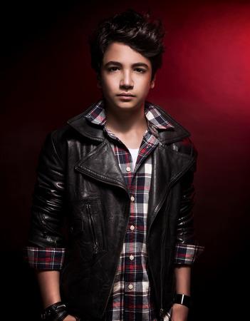 Stijlvolle tiener jongen portret over donkere rode achtergrond, knappe model draagt fashion shirt en lederen jas, funky adolescentie stijl Stockfoto