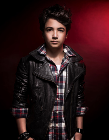 Stylish teen boy portrait over dark red background, handsome model wearing fashion shirt and leather jacket, funky adolescence style