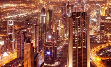 edificio: La ciudad de Dubai en la noche, hermosos edificios modernos brillan luces, vista de pájaro en magnífico paisaje urbano, famoso centro de negocios y viajes, Emiratos Árabes Unidos