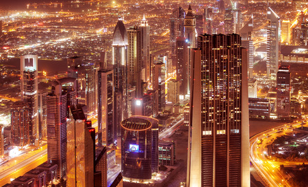 Dubai city at night, beautiful modern buildings  glow lights, bird eye view on gorgeous cityscape, famous business and travel center, United Arab Emirates