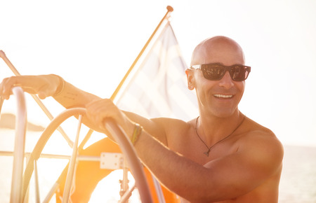 skipper: Portrait of handsome shirtless sailor behind helm of sailboat in bright sunny day, enjoying active summer holidays, happy traveling along sea