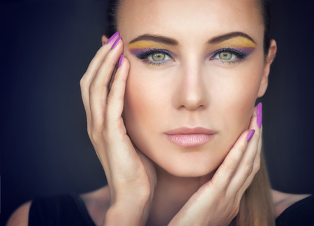 model face: Closeup portrait of a beautiful woman face over dark background, gorgeous model with colorful stylish makeup, fashion look, luxury beauty salon