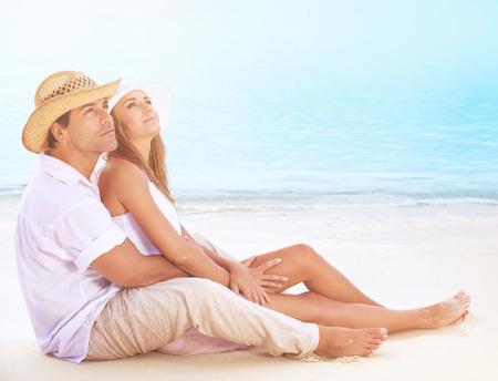 amantes: Amantes felices en la playa, hermosa pareja de j�venes sentados en la costa arenosa y abrazos, so�ador mirando hacia arriba en el cielo y disfrutar de la luna de miel rom�ntica