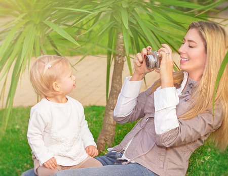 parental love: Cheerful mother taking picture of her cute little daughter in the park, happy young family having fun outdoors, parental love and enjoyment
