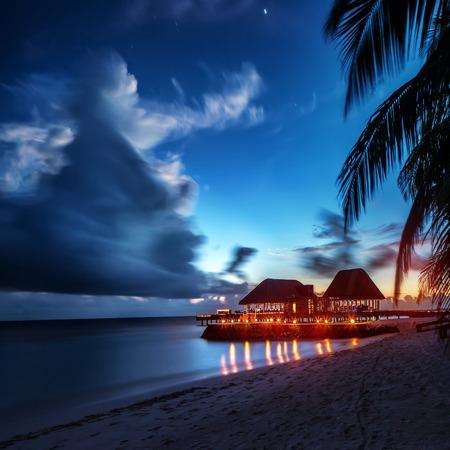 férias: Praia do paraíso da noite, luz brilhante no restaurante sobre a água, lugar romântico para férias de lua de mel, noite de verão na ilha exótica, Maldivas paisagem