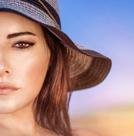 half face: Closeup portrait of gorgeous beautiful arabic woman with perfect makeup wearing stylish hat on the beach, half face, fashion and beauty Stock Photo