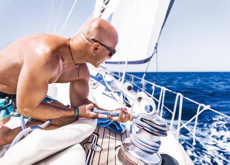 bel homme: Bel homme travaillant sur voilier, torse nu muscl� capitaine corde tirant sur le treuil, l'activit� de l'heure d'�t�, profitant de sport extr�me de l'eau Banque d'images