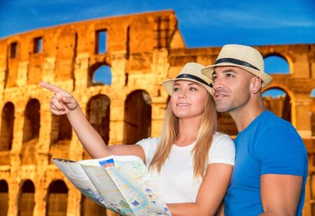 Beautiful active couple with map standing on Coliseum background and looking for right way, travel to Rome and exploring it by themself, Italy Europe photo