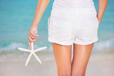 animal body part: Back side of girl standing on the beach, wearing white beach shorts and holding in hand starfish, summer vacation concept