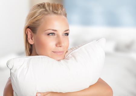 Gelukkig meisje genieten van haar favoriete zacht kussen, tijd doorbrengen thuis, dromerige vrouw met plezier het voorbereiden om te slapen, rustend op comfortabele bedden